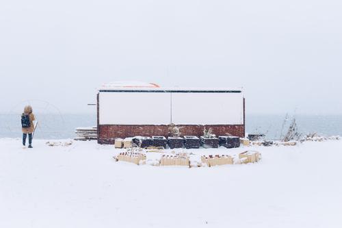 Schneelandschaft am Meer Winter Mädchen Spaziergang laufen Frau Landschaft MEER Wasser Natur kalt Strand Wetter weiß Eis Himmel Hintergrund Bucht Licht reisen