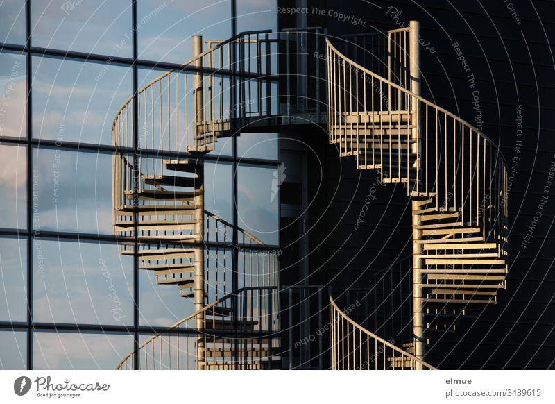 Wendeltreppe in der Abendsonne und in einer Glasfassade gespiegelt Treppe spiegeln Fassade Scheibe Architektur Menschenleer Gebäude Haus Spirale Nottreppe Helix