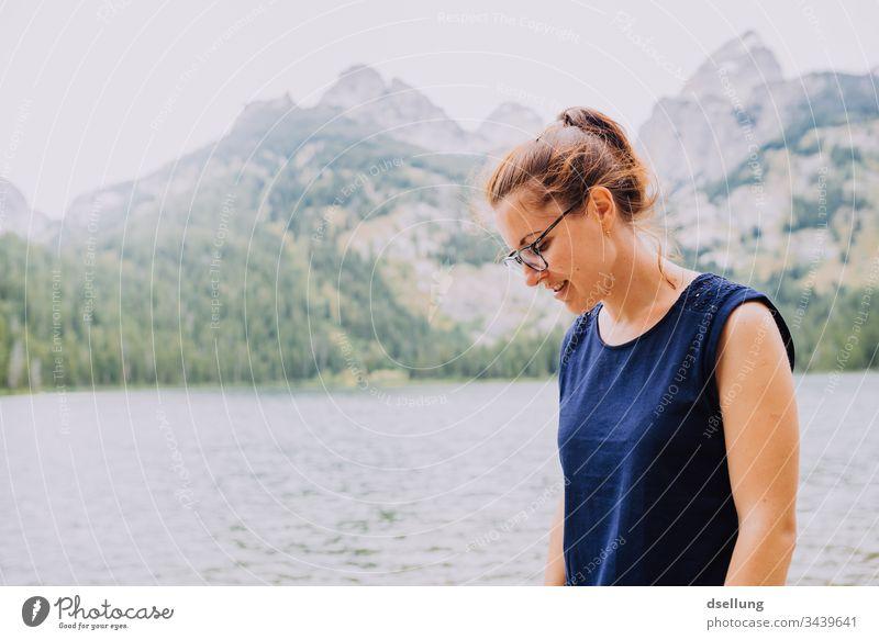 junge Frau schaut lächelnd auf dem Boden vor einem See mit Gipfeln im Hintergrund Jugendliche leuchtend attraktiv 1 Mensch Erwachsene brünett wandern Tourismus
