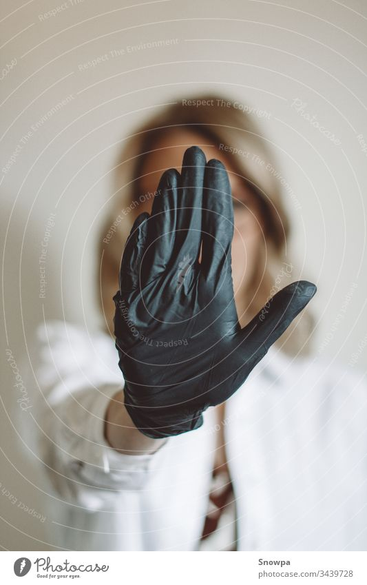 Frau zeigt Stoppschild mit schwarzem Handschuh Handschuhe schwarze Handschuhe Gummihandschuh Arzt Wissenschaftler blond blondes Haar bürsten covid-19