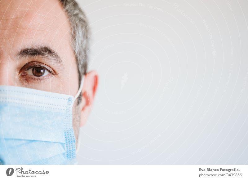 Nahaufnahme eines Arztes, der im Haus eine Schutzmaske und Handschuhe trägt. Coronavirus Covid-19-Konzept Porträt Mann professionell Corona-Virus Krankenhaus