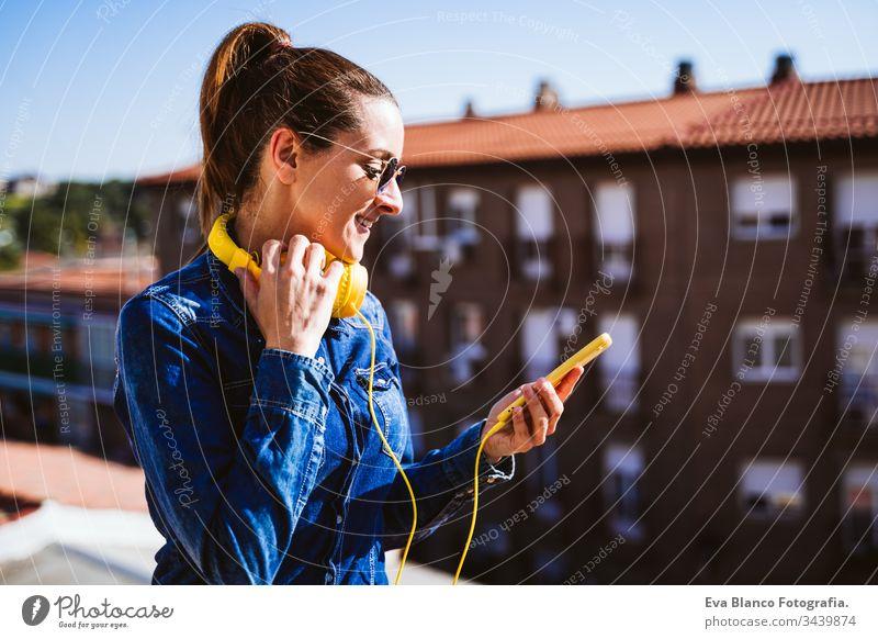 junge Frau, die über ein Mobiltelefon und ein gelbes Headset Musik hört. Spaß und Lebensstil hören Handy Technik & Technologie Terrasse im Freien sonnig