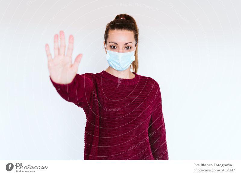 Weiße Frau im Haus, die eine Schutzmaske trägt. Mit der Hand ein Stoppschild machen. coronaviruskonzept covid-19 Coronavirus schützend Mundschutz