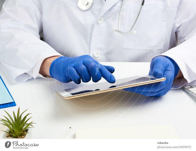 Arzt im weißen Kittel sitzt an einem Tisch, hält ein elektronisches Tablett in der Hand, berührt mit der rechten Hand den Bildschirm Tablette medizinisch