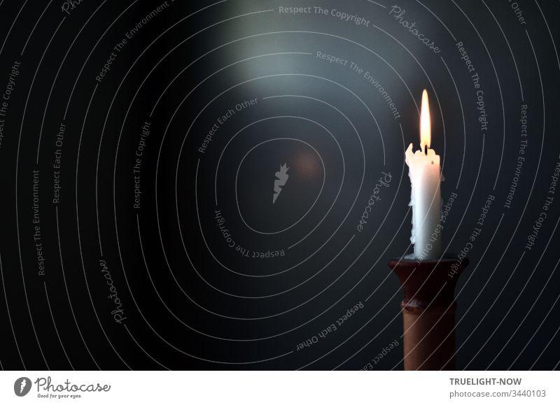 Vor dunklem Hintergrund brennt einsam eine weiße Kerze in einem Terrakotta Kerzenständer Kerzenflamme Kerzenschein Licht Flamme brennen Menschenleer leuchten