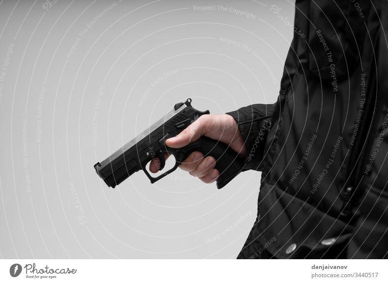 Hand mit Pistole auf weißem Hintergrund Aggression Ziel ak bewaffnet Anschlag Sturmhaube Bandit schwarz Verbrechen Krimineller gefährlich Schußwaffen Gangsterin