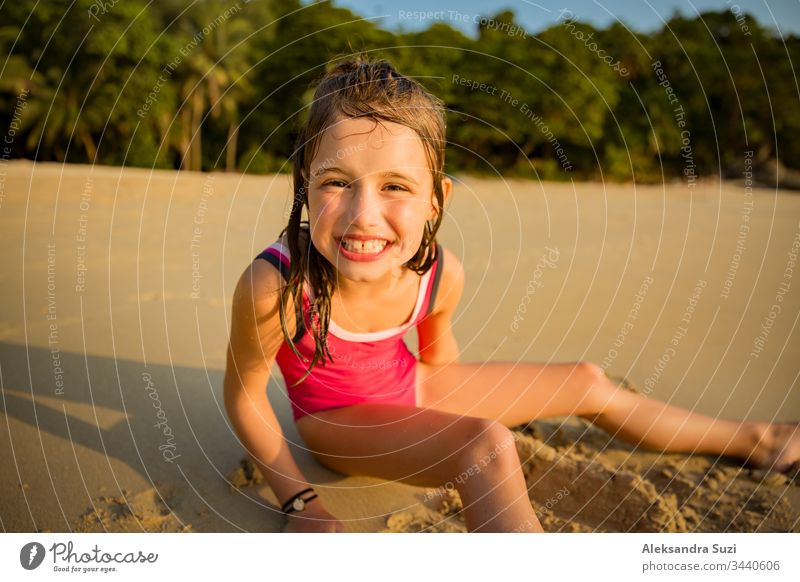 Süßes fröhliches kleines Mädchen, das im Badeanzug am Strand mit Sand spielt, ein Herz zeichnet und schreibt. Wunderschöner Sommersonnenuntergang, Meer, Kokospalmen, malerische exotische Landschaft. Phuket, Thailand
