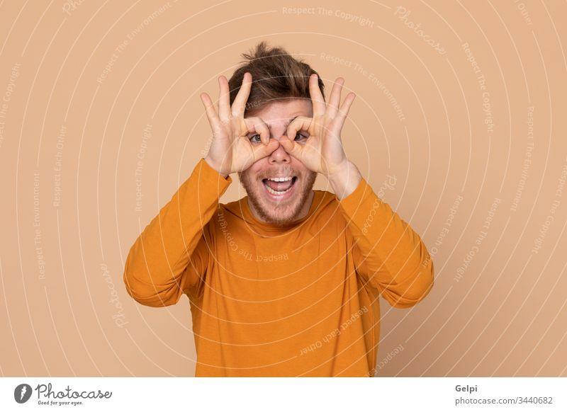 Attraktiver junger Mann Typ gelb orange herausschauen Beobachten Sie sehen beobachten Auge Watchman klatschend Brille Sehvermögen scoffing sich lustig machen