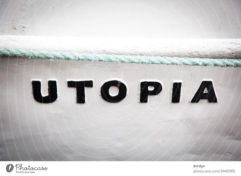 Utopia, Schrift auf einem Boot, bezeichnet ein Land in dem es allen gleichermaßen gut geht,ein Idealzustand für Alle. Schriftzeichen und Buchstaben Begriff
