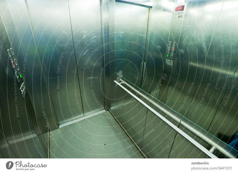 Im Fahrstuhl fahrstuhl lift kabine fahrstuhlkabine liftkabine haus wohnhaos hochhaus stockwerk etage metall glanz geländer stange haltestange balance tür