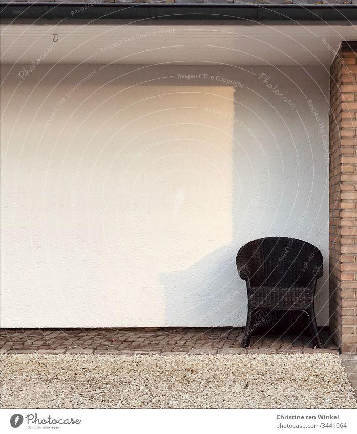 Einsamer Sessel an einer Hauswand Einsamkeit einsam Sitzgelegenheit Sonne Schatten helle Farben warten Möbel Gedeckte Farben Tag trist braun weiß