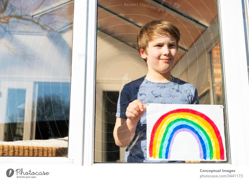 Kaukasischer Junge hält ein Bild eines Regenbogens Kindheit Zeichnung Hoffnung Tagträumen Inspiration Aspiration Kaukasier jung Künstler farbenfroh Aktivität