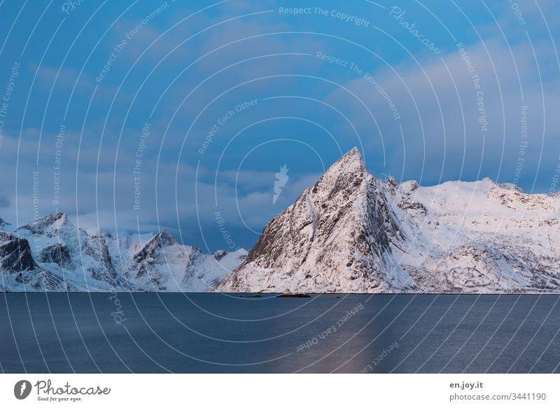 Verschneite Berge am Fjord Sonnenuntergang Schatten Licht & Schatten bewölkt Weitwinkel Gipfel Insel Wolken Himmel Norden Erholung Winterurlaub Meer Schnee