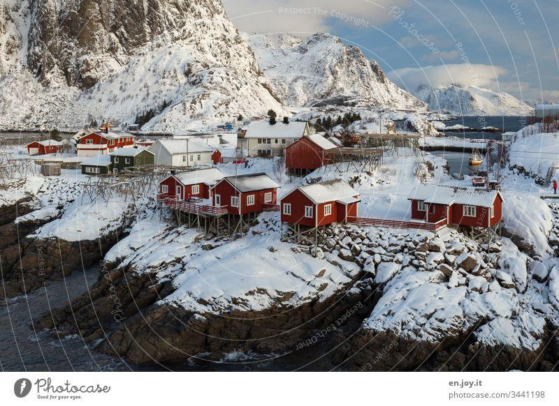 Hamnoy auf den Lofoten mit Aussicht auf die kleinen roten Häuschen die auf verschneiten Felsen stehen Panorama (Aussicht) Reinefjorden Fjord Küste bewölkt