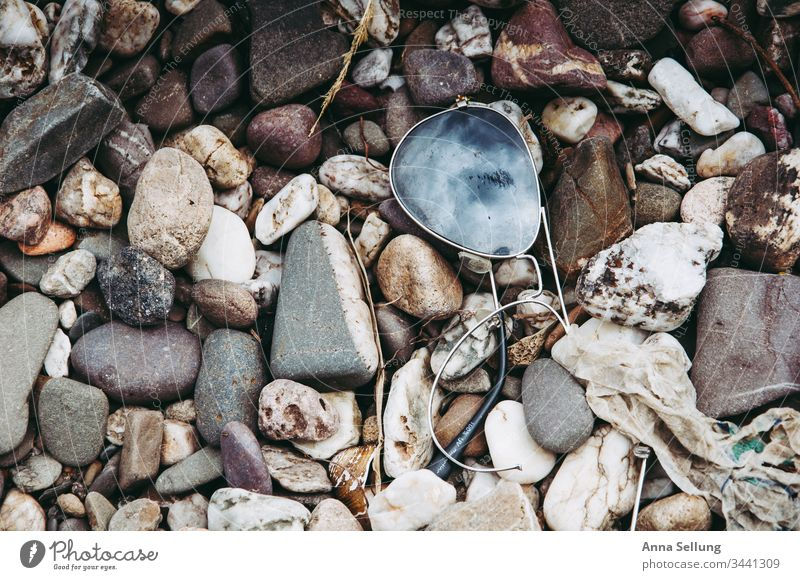Kaputte Sonnenbrille am Steinufer mit Spieglung des Himmels spieglung blau Nahaufnahme grau kaputt Zerbrochenes Fenster zerbrochen defekt Muster Außenaufnahme