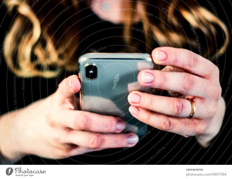 die Hände einer jungen kaukasischen brünetten Frau, während sie ein Smartphone hält, das auf dem Touchscreen tippt. Frauen Handy Beteiligung Menschen