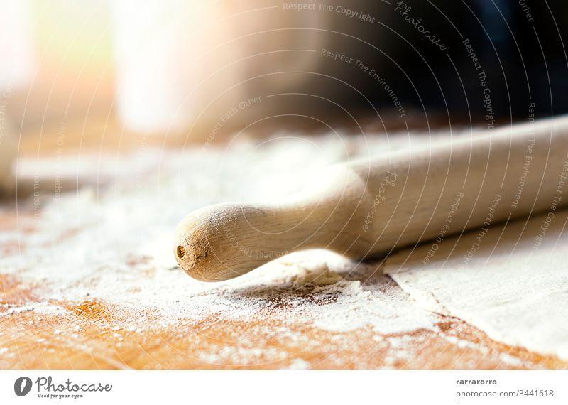 ein Nudelholz über einem Teig auf einem mit Mehl beschmutzten Holzbrett Plan Vorbereitung Bestandteil Rolle traditionell kulinarisch Herstellung Kneten Hefe