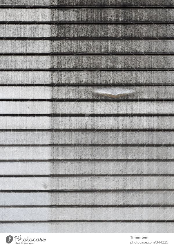Ein Außenseiter. Rolltor Beule Profil Linie Metall dreckig dunkel grau schwarz Gefühle Spuren markant Industrieanlage Gedeckte Farben Außenaufnahme Menschenleer