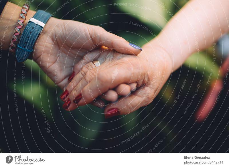 Unerkennbare Großmutter und ihre Enkelin, die mit Liebe die Hand halten. Konzept zum Schutz der Großeltern. Konzepte Händchenhalten Frauen