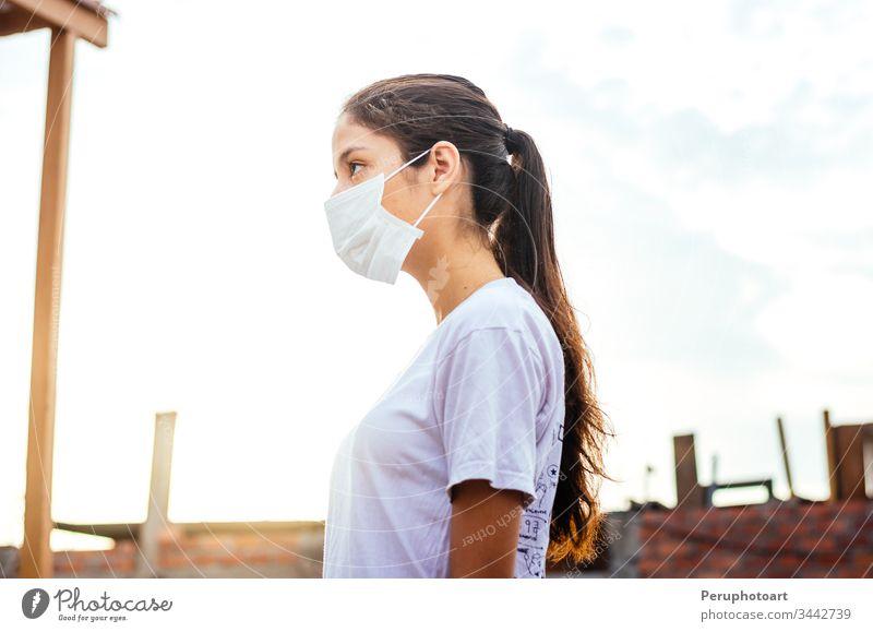 Junge Frau mit einer Maske zum Schutz vor dem Coronavirus COVID-19 an einem sonnigen Tag jung Mundschutz Infektion Seuche covid-19 Erwachsener Krankheit Gesicht