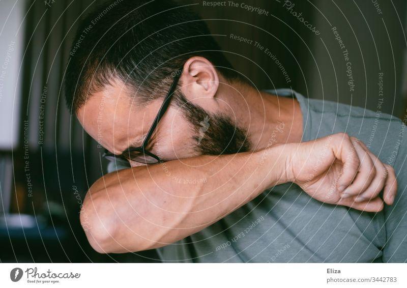 Ein Mann der sich richtig in die Armbeuge niest um die Ansteckung anderer mit dem Corona Virus zu verringern Schützen Corona-Virus Krank Niesen infektiös
