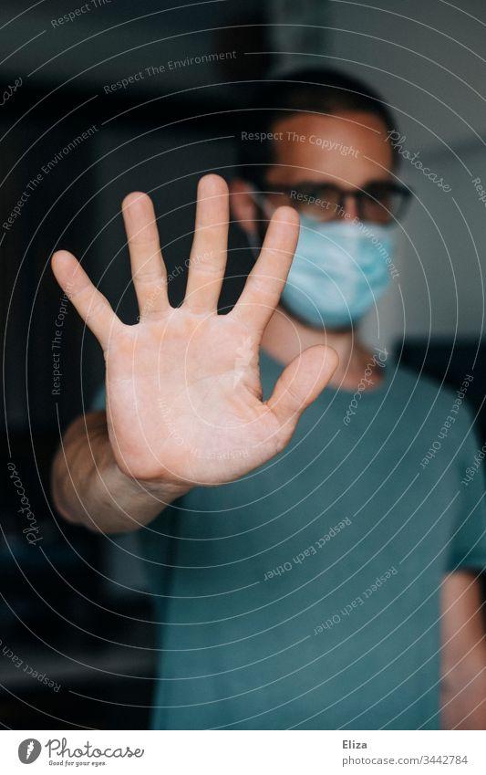 Mann mit Mundschutz Gesichtsmaske streckt während der Corona Pandemie seinen Arm aus um Abstand einzuhalten, weil er ansteckend ist Ansteckend Maske Atemschutz