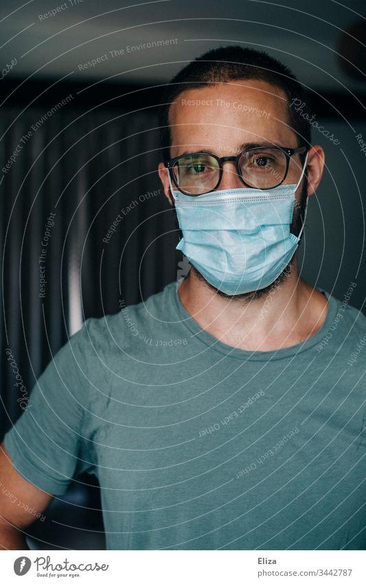 Mann mit Mundschutz Gesichtsmaske blickt während der Corona Pandemie ernst und traurig in die Kamera Ansteckend Maske Atemschutz Coronavirus Schutz Corona-Virus