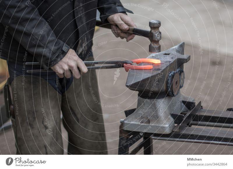 Hufschmied bei der Arbeit am Amboss Hufeisen Pferd schmieden Glut heiß Handwerk Schmied Hammer formen Metall glühend Eisen Schmiede Tradition Werkzeug Stahl