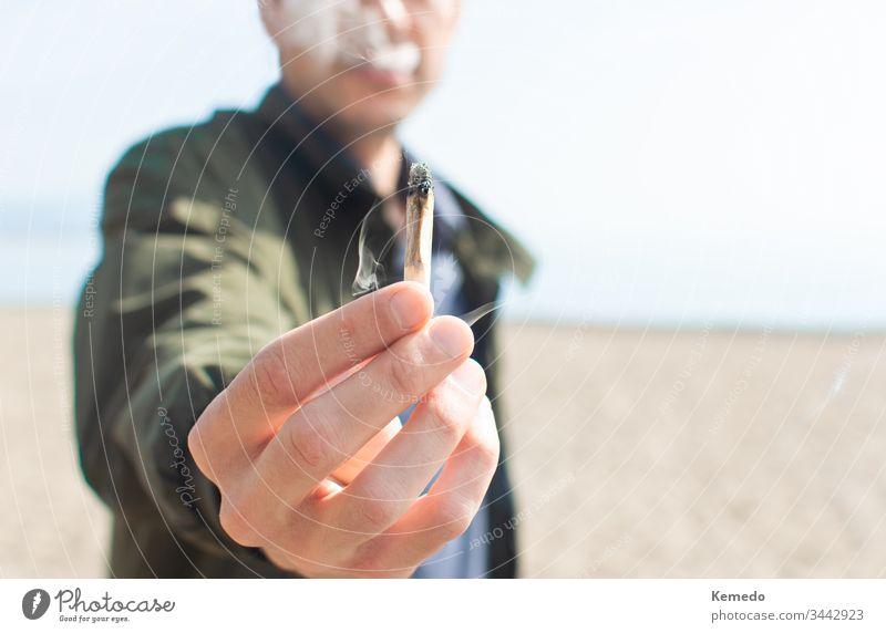 Junger Mann hält einen angezündeten Marihuana-Joint in der Hand, während er am Strand raucht. Hintergrund und Kopierraum rechts verwischen. Gelenk Person