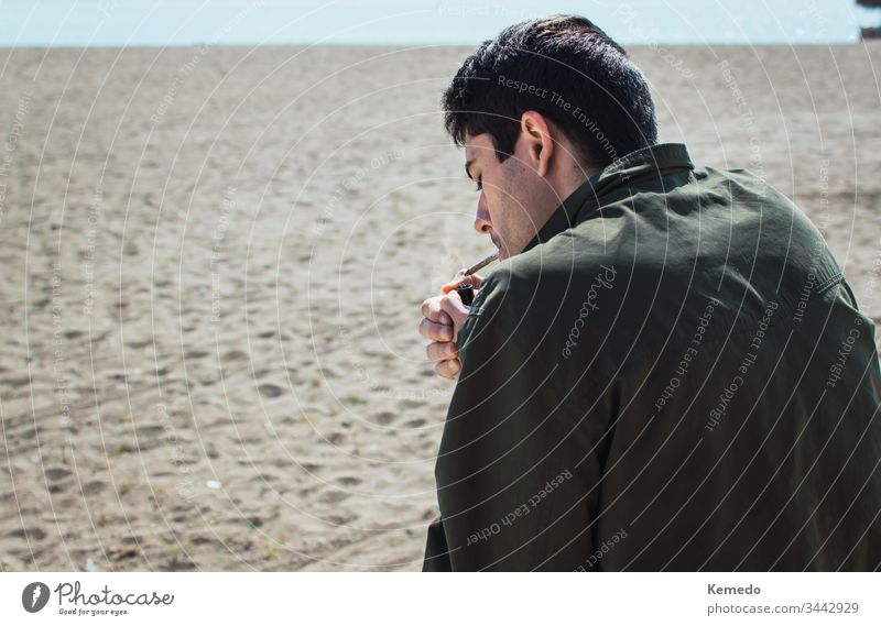 Junger Mann raucht an einem sonnigen Tag einen Marihuana-Joint oder eine Zigarette am Strand. Hintergrund verschwimmen lassen und Kopierraum übrig. Gelenk