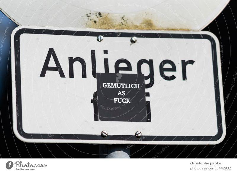 """Aufkleber mit Aufschrift """"gemutlich as fuck"""" auf Straßenschild Anlieger frei Strassenschild gemütlich Schilder & Markierungen Hinweis Menschenleer Außenaufnahme"""