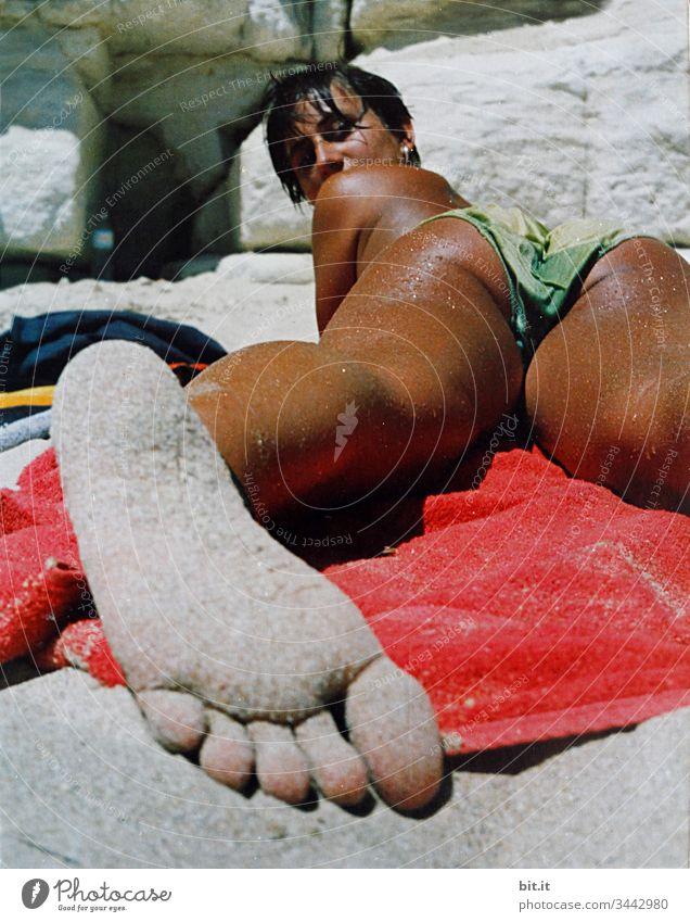 Junge Frau liegt braungebrannt am Strand auf einem Handtuch, barfuß mit sandigem Fuß im Vordergrund und schaut in die Kamera. Sonnenbad Sommer