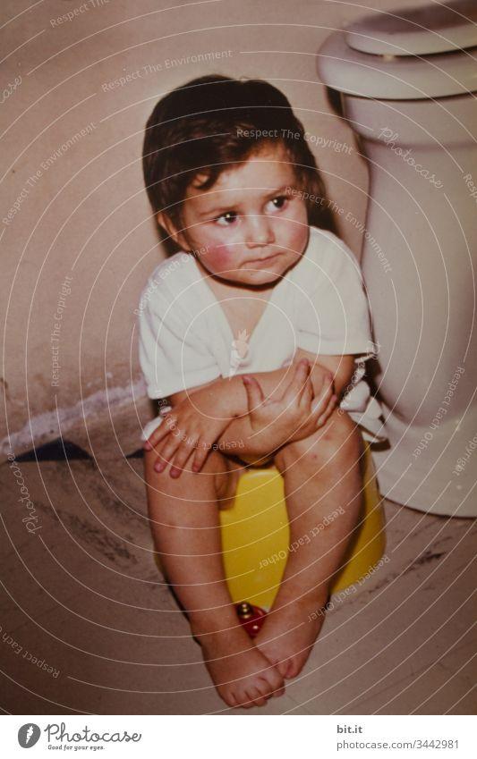 Sinnierend über die Klopapier Situation, sitzt das kleine Mädchen auf dem Töpfchen im Bad vor der Toilette, mit Bettflasche an den nackten Füßen und verschrenkten Armen.