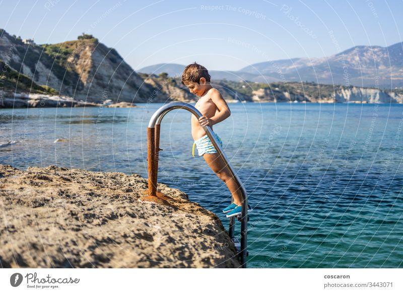 Kleiner Junge auf einer Badeleiter, der zum Baden ins Meer hinuntergeht amandakis schön blau Kind Kindheit übersichtlich Klettern Küste Kristalle niedlich