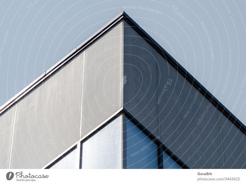Ecke eines grauen Betongebäudes mit Fenstern Architektur Architektur-Hintergrund Blöcke blau Gebäude Großstadt Eckstoß Ecke des Hauses leer Glas sehr wenige