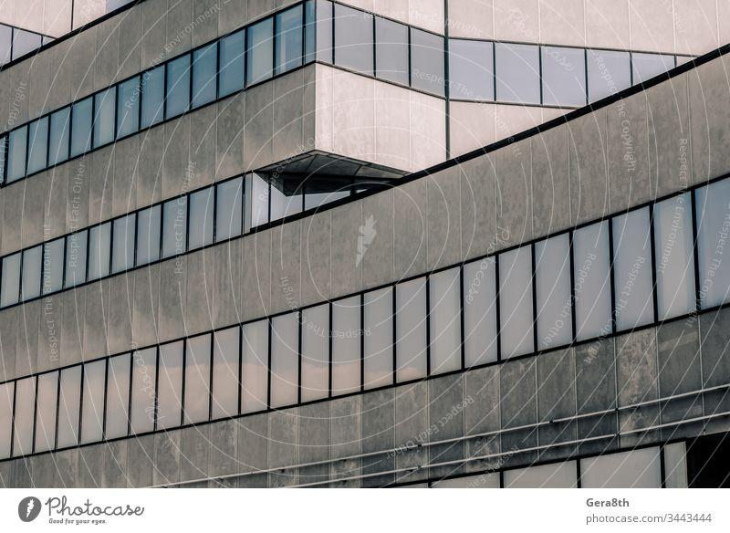 graues hohes Betongebäude mit Spiegelung des Himmels und Wolken in den Fenstern abstrakt Architektur Hintergrund blau Gebäude Business Großstadt leer Stock hoch