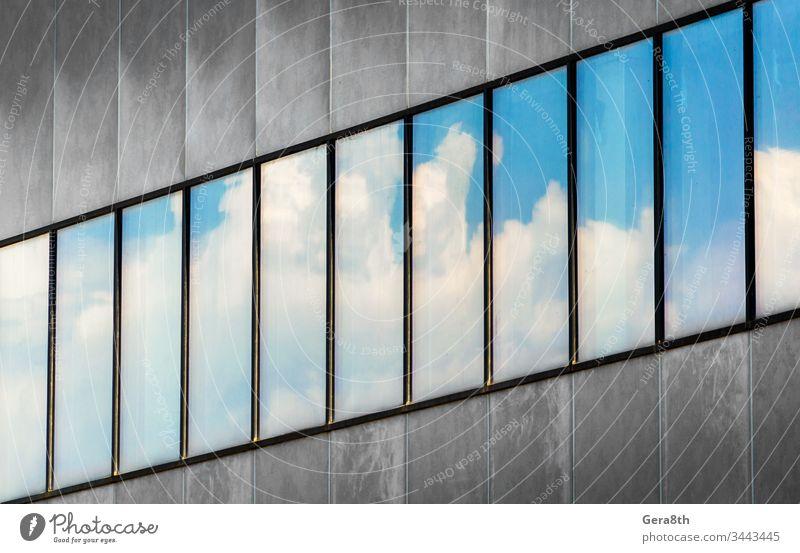 Spiegelung von blauem Himmel und weißen Wolken in den Fenstern eines grauen Betongebäudes abstrakt Architektur Hintergrund Blöcke Blauer Himmel Business