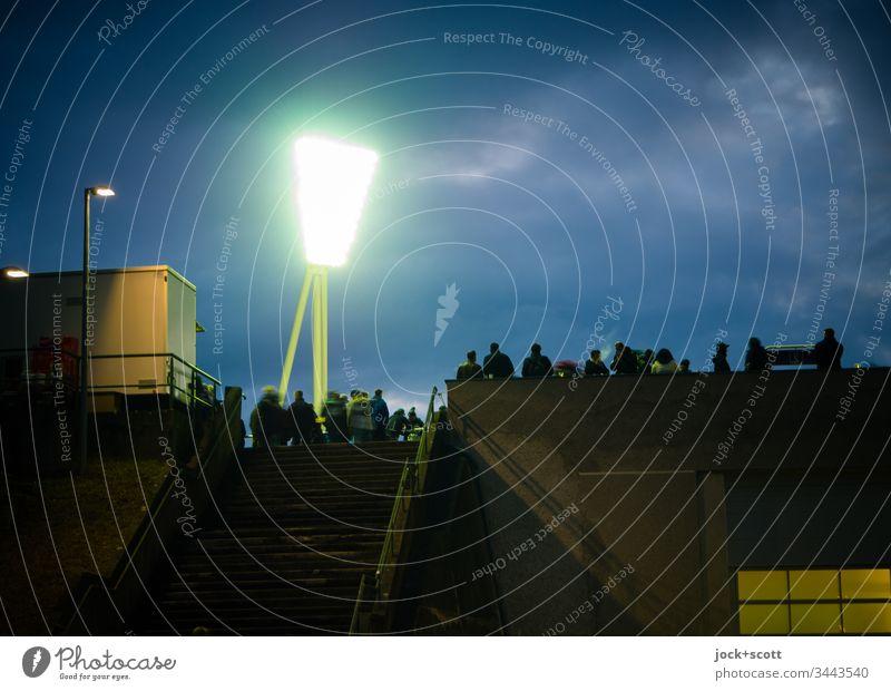 Begegnung im Stadion und im Scheinwerferlicht Dämmerung Abend Kontrast Textfreiraum rechts Farbfoto Außenaufnahme Ventilator kalt dunkel Textfreiraum oben Licht