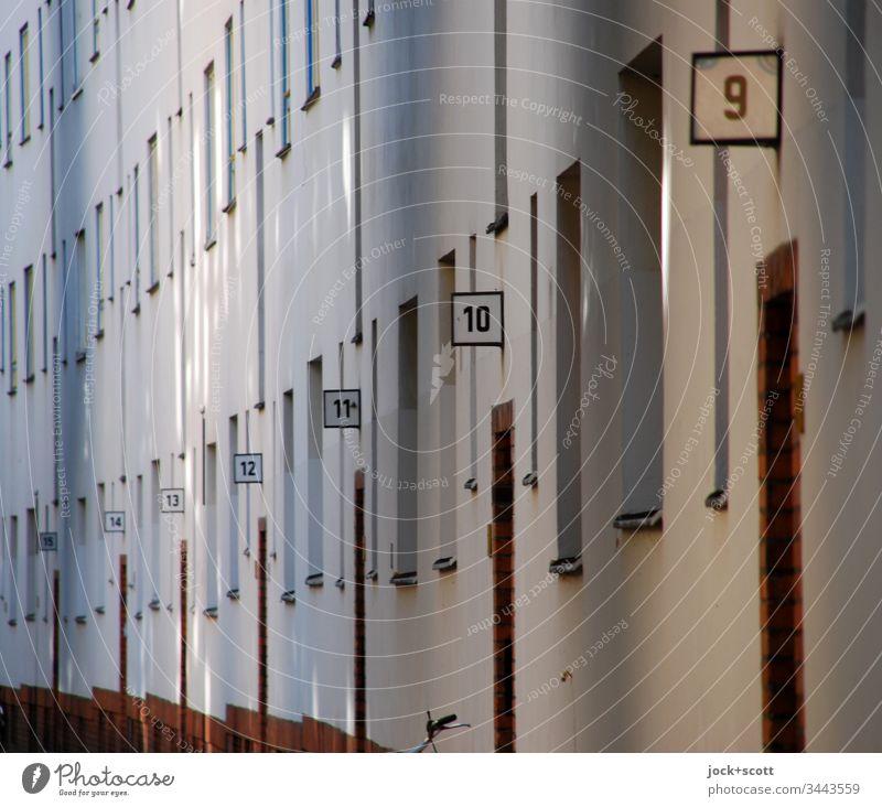 Hausnummern von 15 bis 9 in einer Straße Stadt Perspektive Ordnung Ziffern & Zahlen Fassade Wand Menschenleer Farbfoto Außenaufnahme Tag Mietshaus Fenster Türen