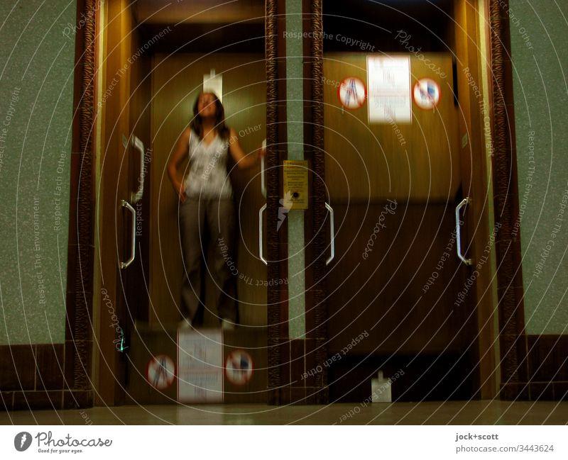 Paternoster nimmt die junge Frau gerne mit einem Lächeln Fahrstuhl Bewegung stehen aufwärts abwärts Gedeckte Farben Erwachsene festhalten langhaarig Warnhinweis