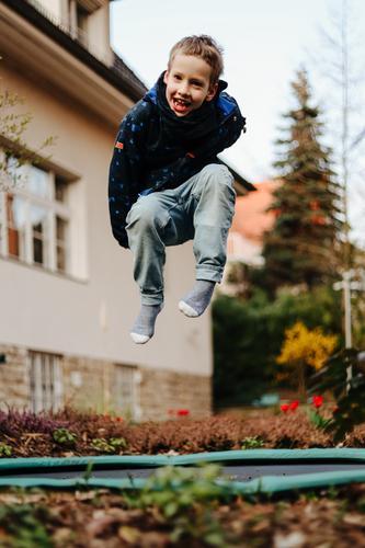 Kleiner Junge lacht und hüpft auf einem Trampolin im Garten eines Hauses klein Kind Schulkind hüpfen springen fliegen Villa Heidekrautgewächse Freude Spielen
