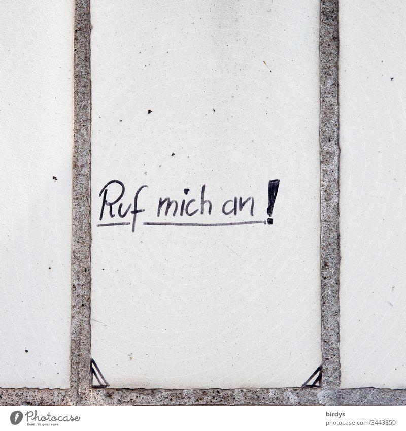 Handschrift auf einer Wand.Bitte um Kontaktaufnahme in Zeiten der Vereinsamung, Hoffnung und Verzweiflung. Ruf mich an ! Aufforderung anrufen Menschenleer