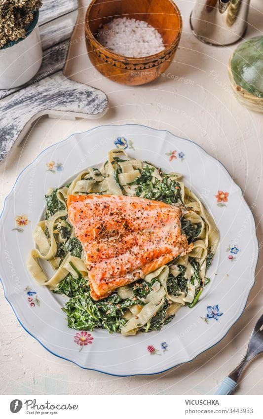 Teller mit Nudeln, Lachs und Spinat auf weißem rustikalem Tischfond. Gesunde Mahlzeit. Diät. Mittagessen. Ansicht von oben Hintergrund Gesundheit Lebensmittel