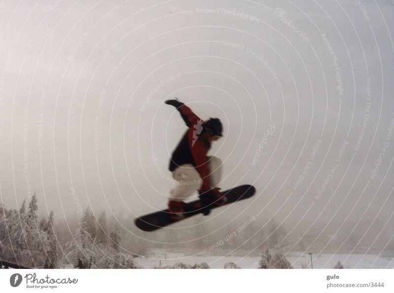 Boardgrab springen Snowboard Nebel Sport Schnee Berge u. Gebirge Snowboarder Snowboarding hoch 1 Außenaufnahme Farbfoto Textfreiraum oben Körperhaltung