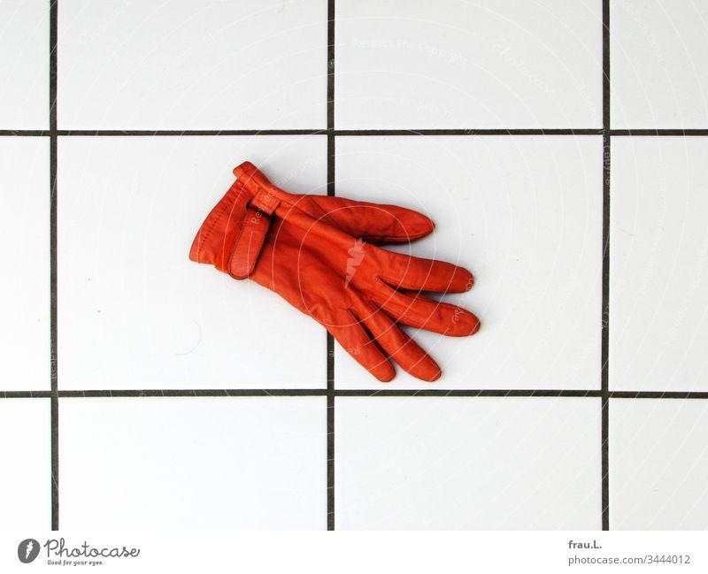 Der orange Handschuh fror auf den kalten Fliesen und er sehnte sich nach seinem Partner. Badezimmer Kacheln fußboden Leder Innenaufnahme Tag Fliesen u. Kacheln