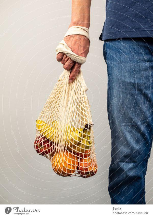 Mann hält wiederverwendbare Tasche mit frischem Obst in seiner Hand, gesunde Ernärhung, plastikfrei einkaufen Frucht Banane orange apfel Vitamin