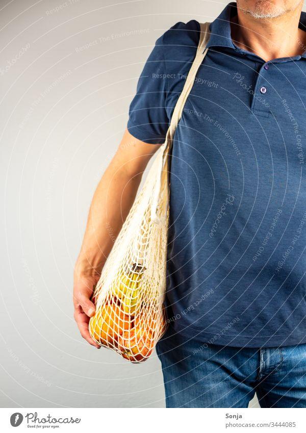 Mann über 40 mit Einkaufsnetz voller Obst über seiner Schulter hängend Banane orange einkaufsnetz Schaufensterpuppe Hand umwelt wiederverwendbare Einkaufstasche