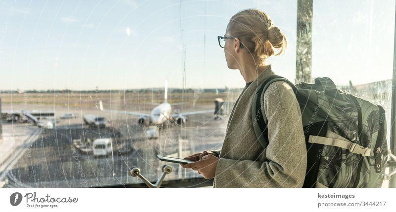 Junge Frau steht in der Nähe des Flughafenfensters, hält ihr Handy in der Hand, trägt einen Reiserucksack und geht zu Fuß zum Lounge-Bereich. Reisende Frau sucht Online-Karte am Flughafen