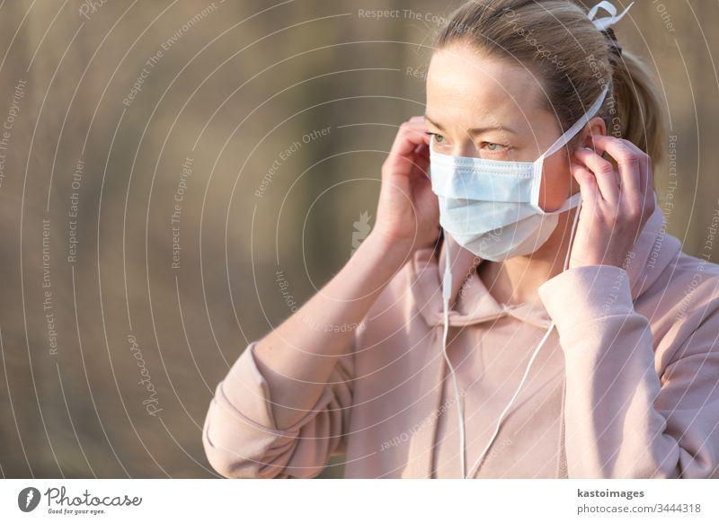 Porträt einer kaukasischen, sportlichen Frau, die eine medizinische Schutzmaske trägt, während sie im Park spazieren geht, sich entspannt und Musik hört. Der Corona-Virus, oder Covid-19, verbreitet sich weltweit.