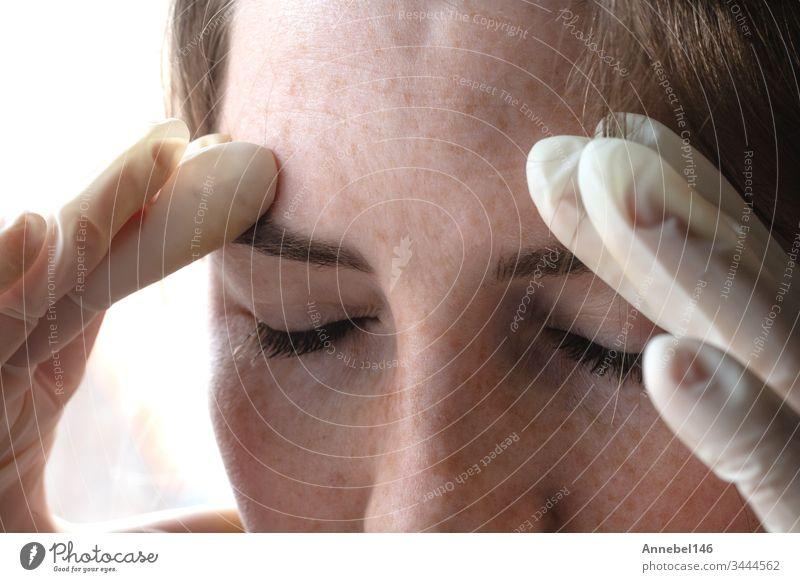 Frau mit Latexhandschuhen blickt durch Coronavirus, Covid-19-Selbstisolierung oder Depression gestresst nach unten - Porträt in Nahaufnahme medizinisch Medizin